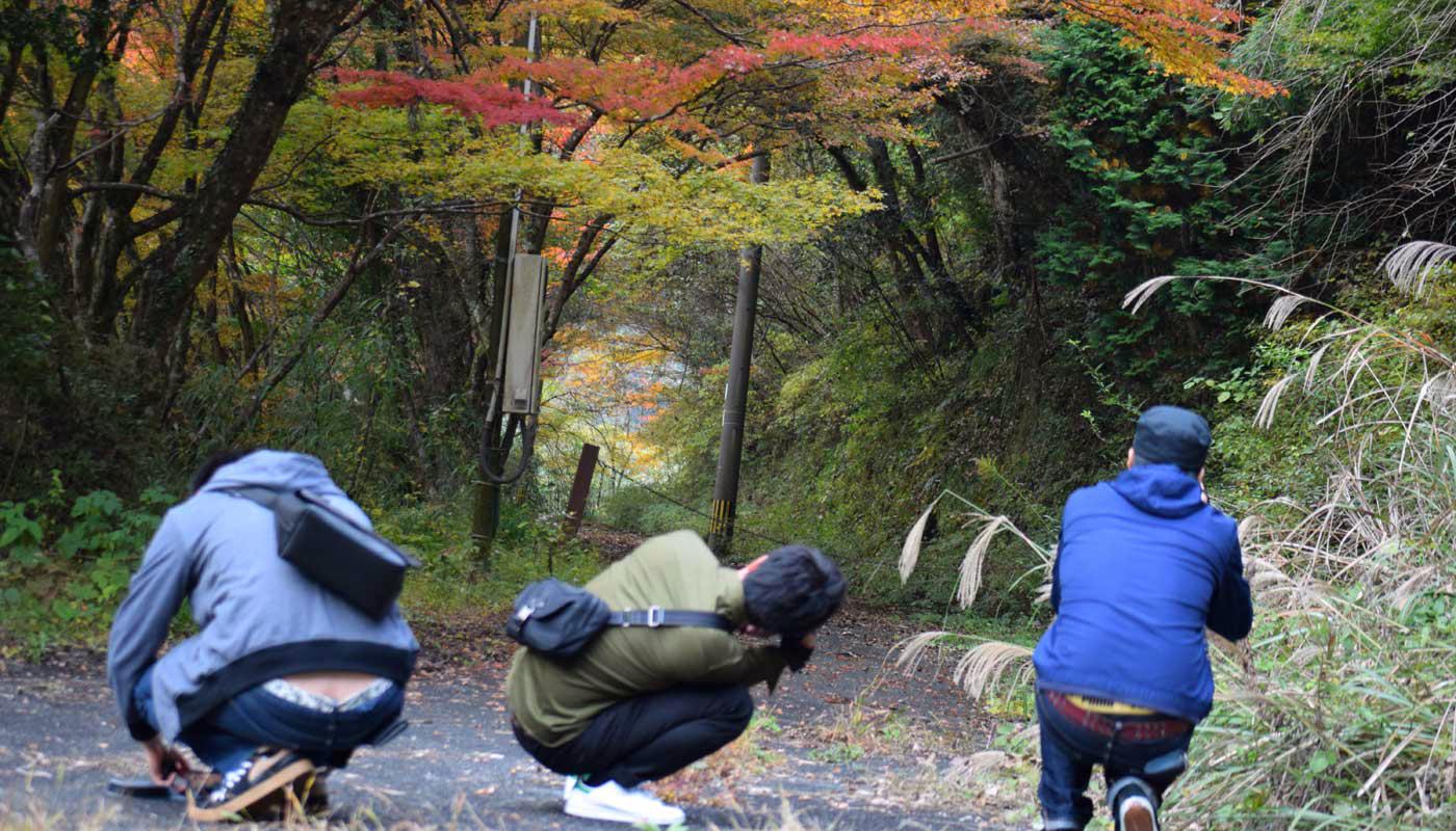 Tre giovani cacciatori d'aceri in appostamento presso i monti Yabakei. Metà di novembre, prefettura di Oita.