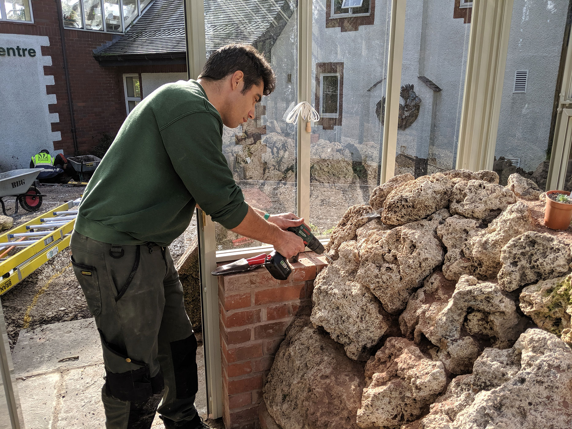 Drilling in and in-between tufa rocks in order to create planting holes.